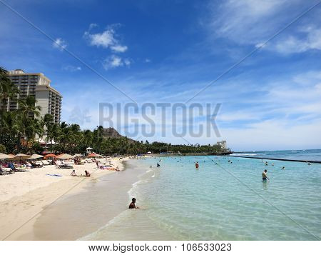 People Play In The Water And Hang Out On The Beach In World Famous Tourist Area Waikiki On A Beautif