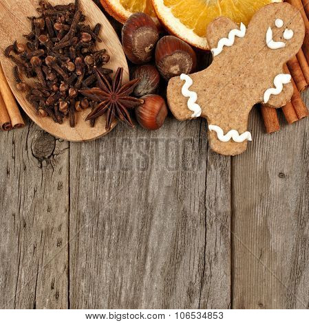 Christmas baking ingredients and gingerbread man border over rustic wood