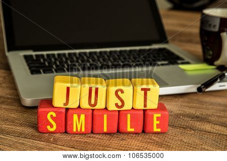 Just Smile written on a wooden cube in front of a laptop