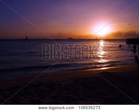 People Play In Water With Dramatic Sunset On Kaimana Beach