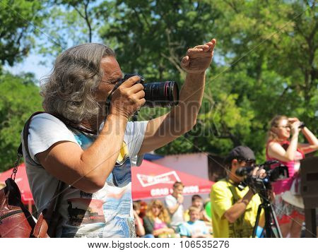 Odessa - May 30, 2015: The Gray-haired Tanned Male Photographer At Work In The Park, Sunny Day May 3