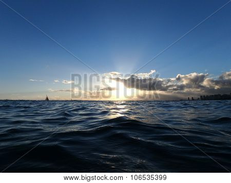 Sunset Light Shines Through The Clouds As Waves Ripples On The Ocean Waters Of Waikiki