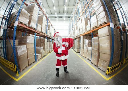 Santa Claus with red sack in storehouse full of presents