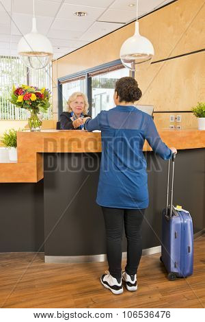 young woman, with a carry on suitcase next to her, handing over her passport, registering, during checkin at a hotel, where a senior receptionist provides customer service