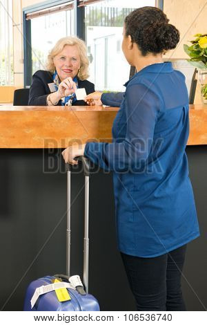 Friendly receptionist behind a counter in a hotel lobby, handing over an electronic key card to a guest with a suitcase during check in after arrival.