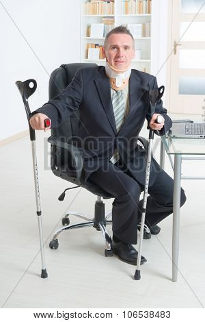 Businessman at work wearing neck brace with crutches