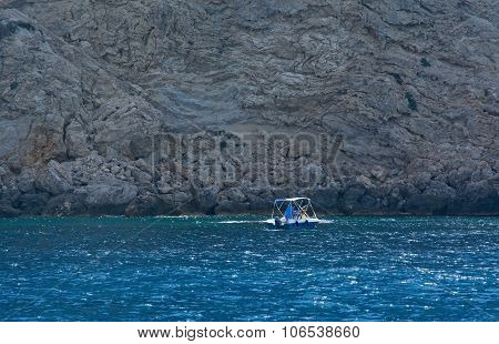 Small boat by steep limestone wall