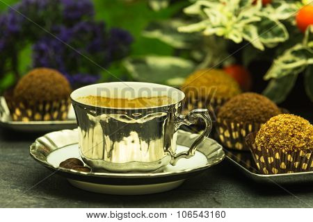 Fresh Espresso Coffee In Luxury Cup With A Few Chocolate Candies In The Garden Im Fronf Of Flowers