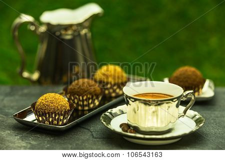 Fresh Espresso Coffee In Luxury Cup With A Few Chocolate Candies In The Garden