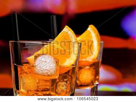 Detail Of Glasses Of Spritz Aperitif Aperol Cocktail With Orange Slices And Ice Cubes On Bar Table,
