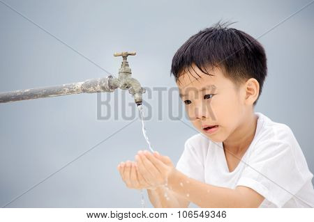 Boy washing from old faucet