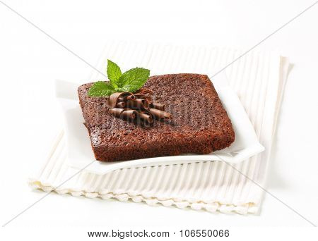 chocolate brownie cake on white square plate and place mat