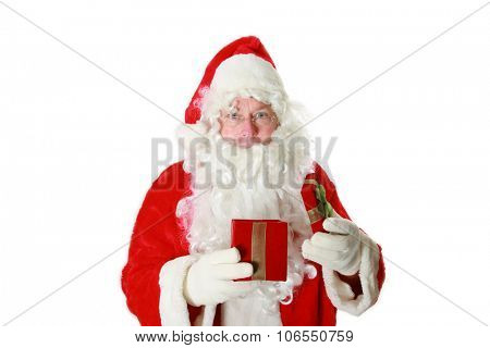 Santa Claus holds a Red Velvet Christmas Present filled with an unknown surprise for someone for Christmas this year. You decide what is inside. Isolated on white with room for your text.