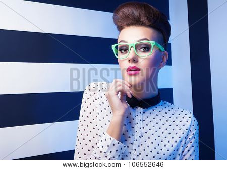 Attractive young surprised woman wearing glasses on stripy background, beauty and fashion concept