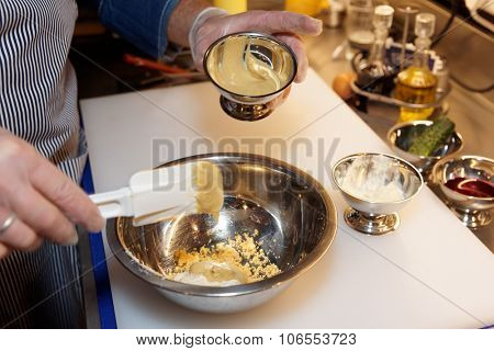 Chef is cooking dressing of mustard, eggs and horseradish
