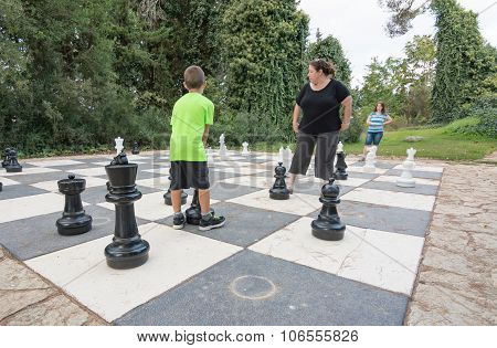 Sister And Brother Playing Giant Outdoor Chess