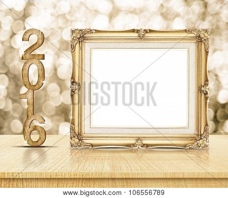 Golden Vintage Frame With 2016 Year Wood Texture With Sparkling Gold Bokeh Wall And Wooden Table