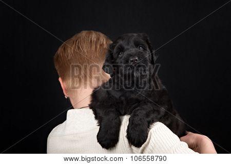 puppy big black terrier and women in dark studio