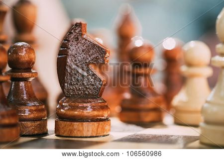 Old Wooden Brown Chess Knight and Pawns Standing On Chessboard
