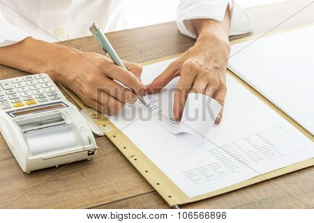 Female Accountant Calculating And Reviewing Numbers On A Receipt