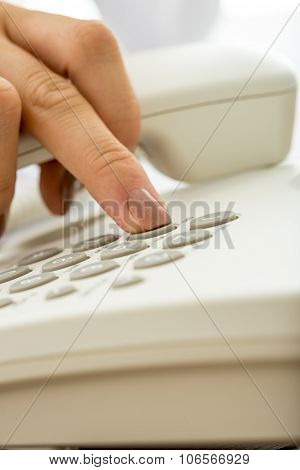 Closeup Of Female Hand Dialing A Telephone Number On A White Landline Phone