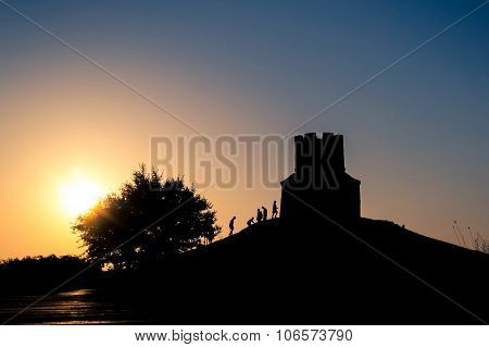 Sunset Silhouettes Of A Medieval Church On A Hill, Tree And People Climbing