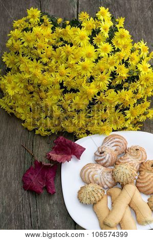 Bouquet Of Yellow Flowers, Red Leaf And Plate With Cookies, On A Wooden Table
