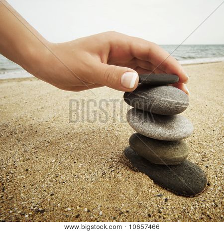 Woman hand touching stones on the beach