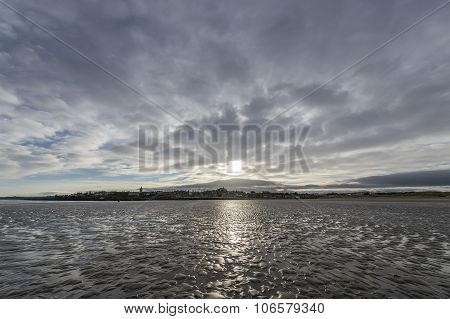 A wide angle seascape vista with St Andrews in the background in Scotland