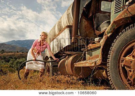 Attractive blond woman filling gas tank of an old truck