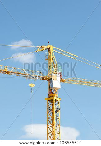 Yellow Industrial Crane And Blue Sky On Construction Site Or Seaport