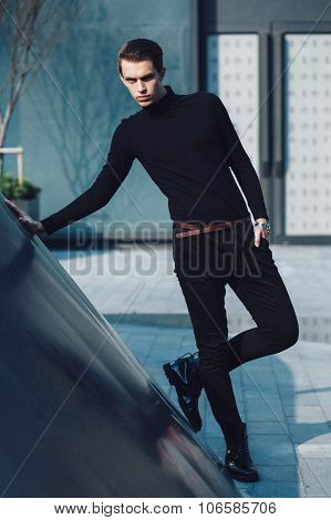 Man model in strict black dress near modern architectural environment.