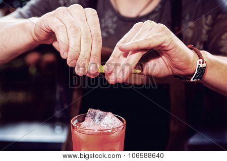 Bartender is adding zest to cocktail, toned image