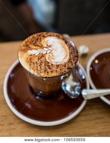 A beautiful glass of mocha coffee with a rosetta design on the top