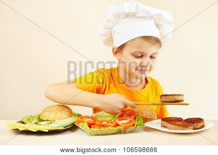 Little funny chef puts meat on hamburger