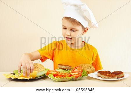 Little boy in chefs hat puts cheese on hamburger
