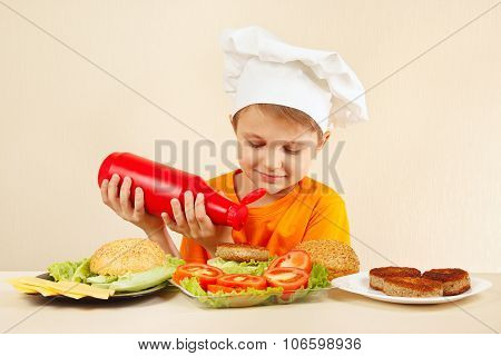 Little boy in chefs hat puts ketchup on hamburger
