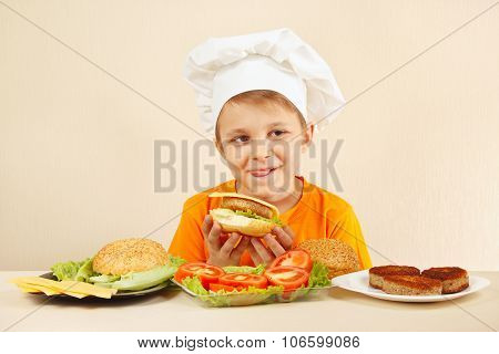 Little funny chef appetizing licked near cooked hamburger