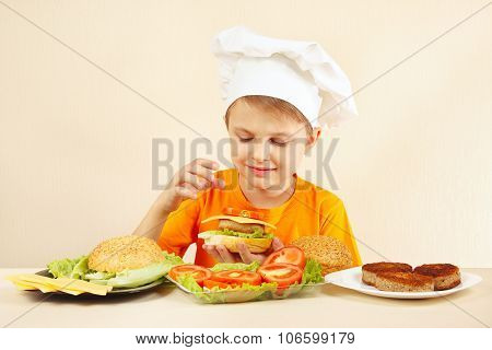 Little smiling boy in chefs hat puts tomato on hamburger