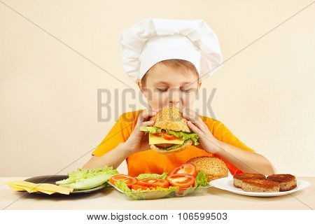 Little boy in chefs hat is tasting cooked hamburger