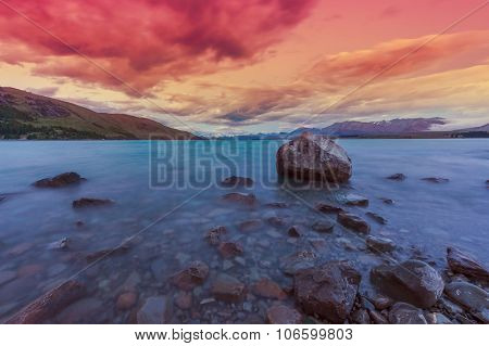 Beautiful dramatic sunset over the incredibly blue lake Tekapo with mountains, Southern Alps, on the horizon. New Zealand