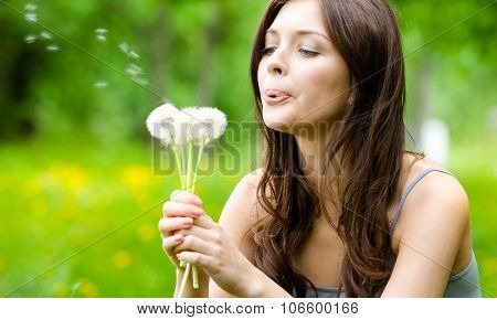 Beautiful woman blows dandelions in the park. Concept of nature and rest