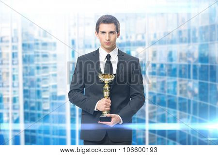 Portrait of business man with gold cup, blue background. Concept of leadership and success
