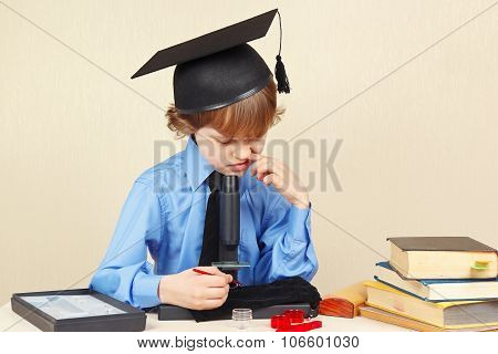 Little boy in academic hat funny thought seeing something in microscope
