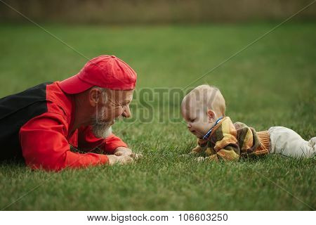 grandfather and grandson lying on grass