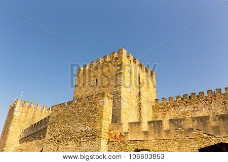 Tower and walls of an old castle agains blue sky