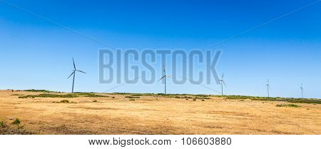 Windmills in the field against clear sky