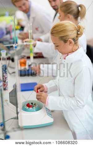 Female technicians work with prepare test tubes for shaker in laboratory