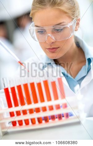Female chemical technician analyzing red fluid in test tubes