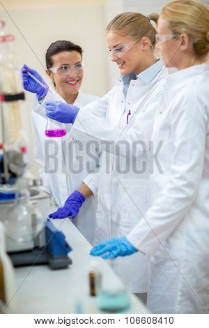 Young chemical assistants taking sample and analyzing fluid from flask in laboratory